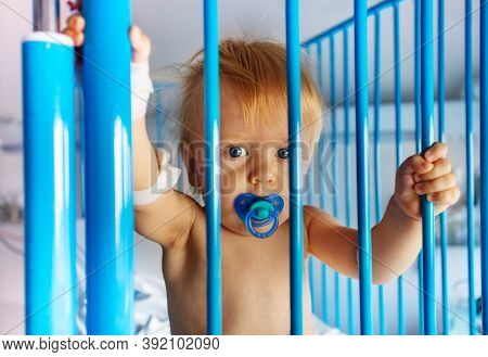 Close Photo Portrait Of A Little Toddler Stand In Hospital Bed With Frame, Catheter In His Hand Hold