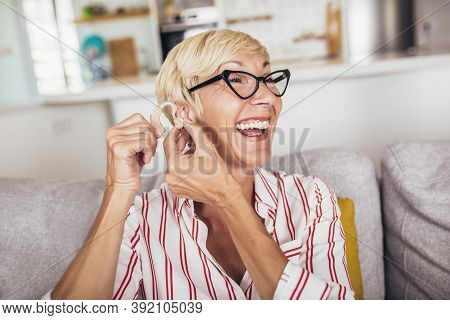 Mature Woman With Hearing Aid Indoors Smiling