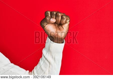 Arm and hand of african american black young man over red isolated background doing protest and revolution gesture, fist expressing force and power