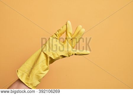 Hand of caucasian young man with cleaning glove over isolated yellow background snapping fingers for success, easy and click symbol gesture with hand