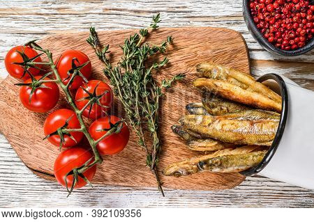 Whole Fried Capelin Fish Served On Cutting Board. White Background. Top View