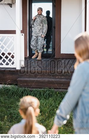 Happy Military Serviceman Standing Near Back Door On Threshold With Blurred Woman And Girl On Foregr