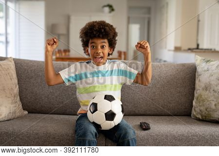 African American boy spending time at home, in living room, sitting on sofa with a football, watching sports on TV, cheering and raising fists in victory. Child spending quality time at home alone.