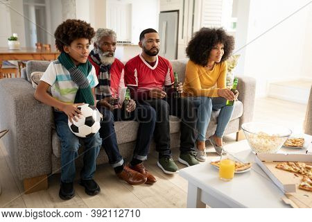 Multi generation African American family at home sitting on sofa in living room, watching sports on TV concentrating. Family spending quality time at home together in slow motion.