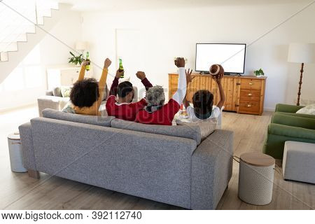Multi generation African American family at home sitting on sofa in living room, watching sports on TV cheering with arms in the air. Family spending quality time at home together in slow motion.