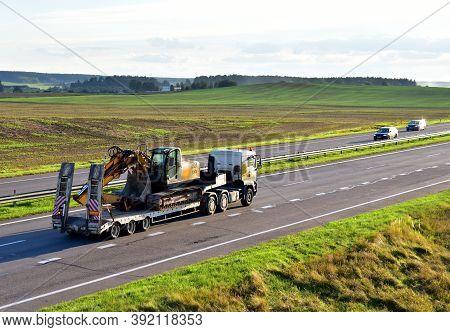 Trailer Truck With Long Platform Transport The Excavator On Highway. Earth Mover Backhoe On Heavy Du