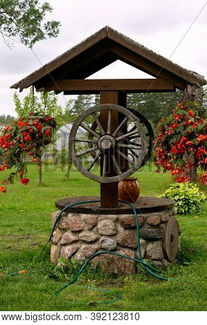 Renovated Old Classic Water Well. The Well, Which Is Decorated With Flower Pots With Red Begonia.