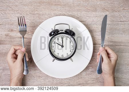 Hands Holding Knife And Fork Above Alarm Clock On White Plate On Wooden Table Background. Intermitte