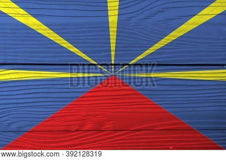 Flag Of Reunion On Wooden Wall Background. Grunge Reunion Flag Texture, Red Yellow And Blue Color.