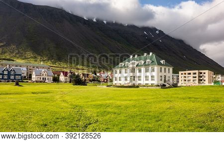 Isafjordur, Iceland - July 7, 2014: White Isafjordur Culture House On A Green Meadow At Sunny Day Wi