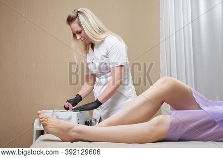 Wax Heater With Hot Yellow Wax On Wooden Spatula In Human Hand. Hot Wax For Depilation. Salon Equipm