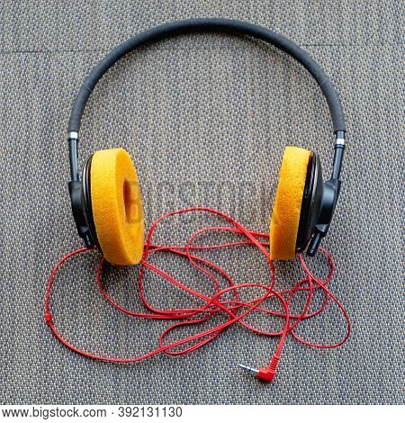 Old Used Headphones With Sponge Cushions And Red Wire
