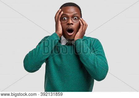 Photo Of Astonished Dark Skinned Guy Opens Mouth Widely, Exclaims With Horrified Expression, Dressed