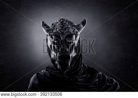 Demon with horned helmet in the dark