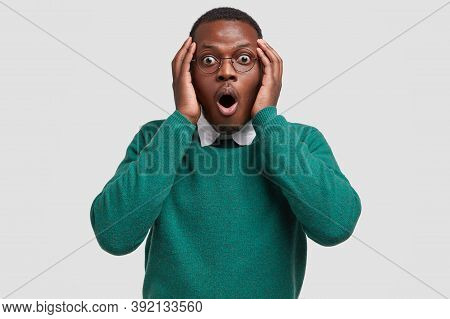 Waist Up Shot Of Shocked Terrified Black Masculine Adult Gasps And Stares In Stupor, Keeps Both Hand