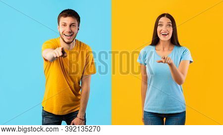 Hey, You. Portrait Of Cheerful Casual Couple Pointing Fingers At Camera, Standing Isolated Over Yell