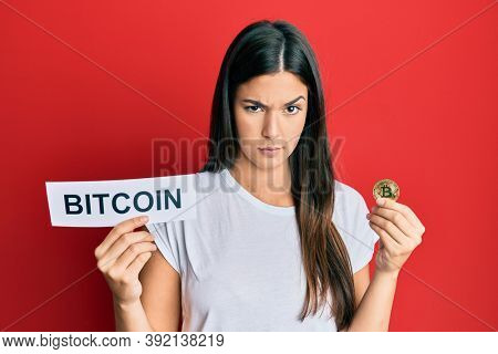 Young brunette woman holding bitcoin virtual money skeptic and nervous, frowning upset because of problem. negative person.