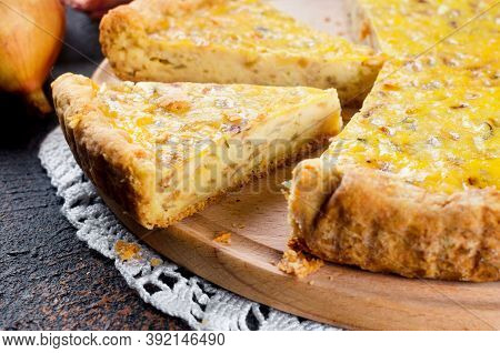 Traditional French Homemade Onion Pie Or Quiche. Open Pie With Cheese And Onion On Round Board On Da
