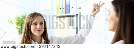 Portrait Of Businesswoman Pointing With Tender Hand. Joyful Female Sitting At Workplace With Colleag
