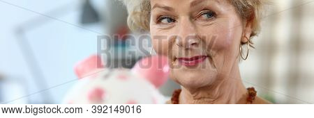 Close-up Of Attractive Elderly Woman Holding Piggy Bank For Money. Colourful Container For Coins And