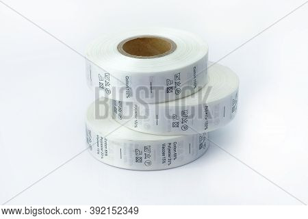 Clothing Care Labels. Clothing Labels, Sewing Accessories. White Skeins, A Roll Of Ribbon With Infor