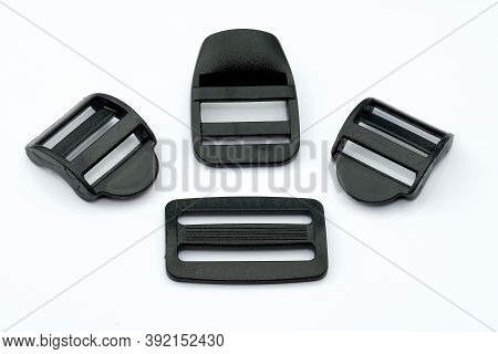 Black Plastic Buckles For A Belt On A White Background. Plastic Straps Of Different Widths For The S