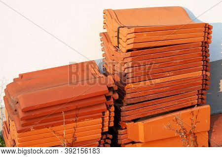 Roof Tiles Of Terracotta In Stacks Next To The Wall Of A Building Under Renovation