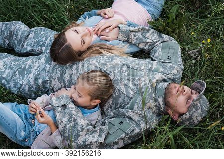 Overhead View Of Military Serviceman Resting And Embracing Wife And Daughter, While Lying On Grass,
