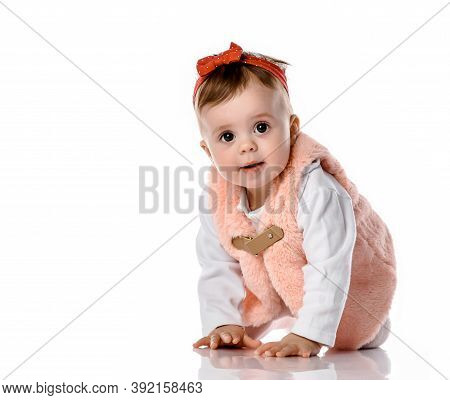 Small Cute Cheerful Baby Girl In Warm Comfortable Vest Crawling Isolated On Floor Studio Background.