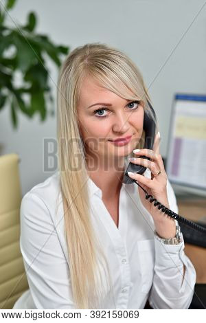 Portrait Of A Cute Young Blonde Business Woman In A White Blouse Smiling With A Telephone Receiver I