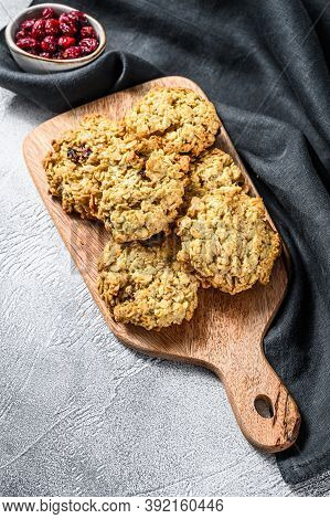 Freshly Baked Cranberry Oatmeal Cookies On Wooden Cutting Board. White Background. Top View