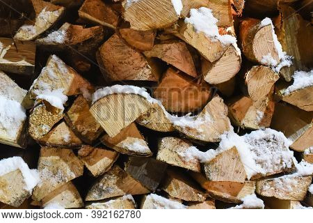Stack Of Chopped Firewood Outdoors Covered With Snow In Cold Winter Weather