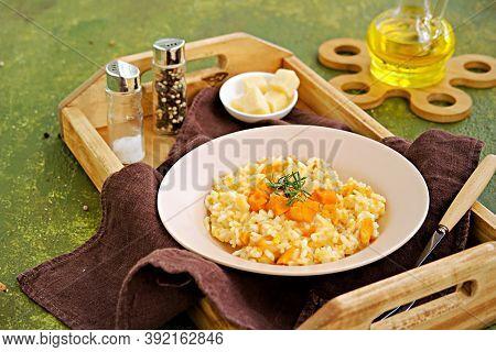 Vegetarian Pumpkin Risotto In A Beige Ceramic Plate On A Green Concrete Background. Italian Food. Pu