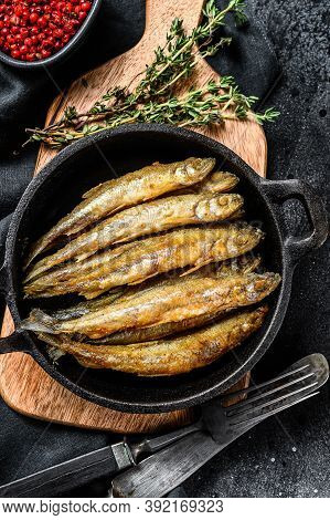 Fried Smelt In The Pan On The Table With Tomatoes And Pepper. Black Background. Top View.