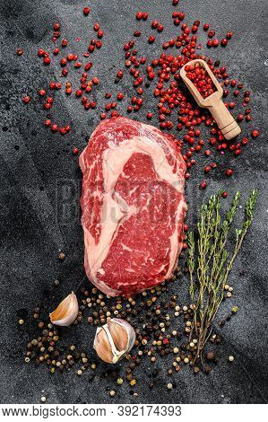 Raw Fresh Meat Ribeye Steak With Seasoning. Rib Eye Beef Steak. Black Background. Top View