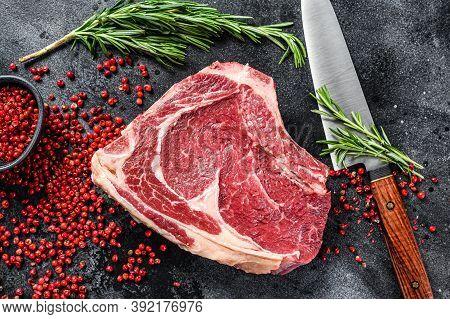 Ribeye On The Bone Or Cowboy Steak. Raw Marble Beef. Black Background. Top View