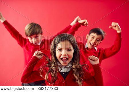 Portrait Of Excited Elementary School Pupils Wearing Uniform Having Fun On Red Studio Background