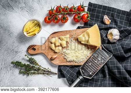 Grated Parmesan Cheese And Metal Grater On Wooden Cutting Board. Gray Background. Top View