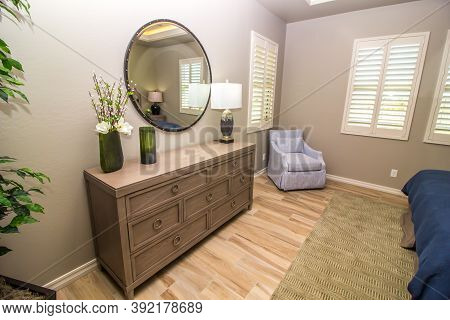 Guest Bedroom With Round Mirror, Dresser & Arm Chair