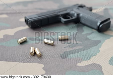 9mm Bullets And Pistol Lie On Camouflage Green Fabric. A Set Shooting Range Items Or A Self-defense