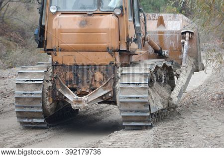 Quarry Aggregate With Heavy Duty Machinery. Caterpillar Loader Excavator With Backhoe Driving To Con