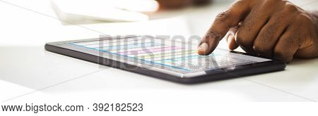 African American Working With Spreadsheet Data On Tablet