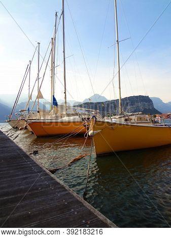 Yellow Sail Boats Moored At Dock On Lake