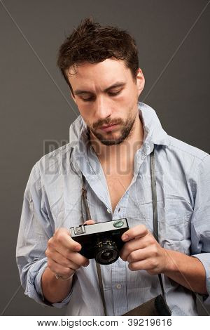 A young man (journalist, newsman) holds film camera.