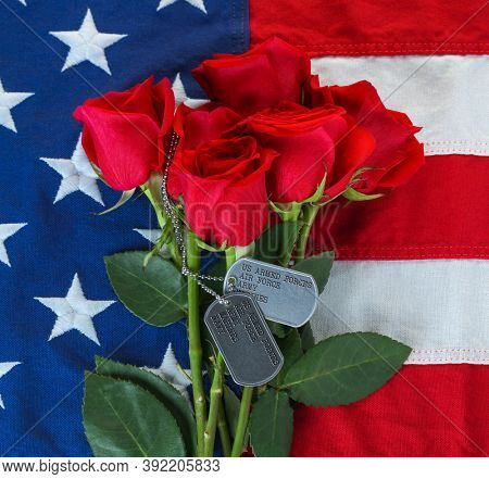 American flag with roses and military dog tags with text listing military branches