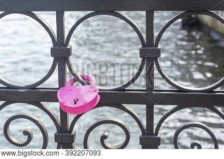 Pink Padlock In The Shape Of Heart Closed By Newlyweds On Their Wedding Day. Symbol Of Eternal Love