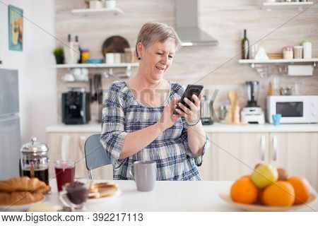 Senior Woman Using Mobile Gadget In The Kitchen. Authentic Elderly Person Using Modern Smartphone In