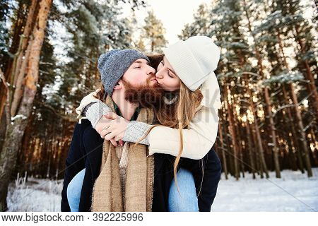 Happy Kissing Couple. Man Giving Woman Piggyback Ride On Winter Vacation In Snowy Forest. Young Coup