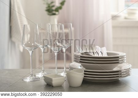 Set Of Clean Dishware, Cutlery And Wineglasses On Grey Table Indoors