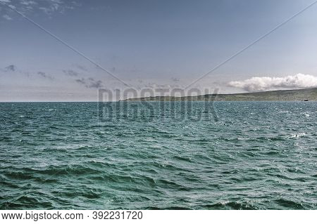 Seascape. Blue Sea And Mountain. The Wind Blows Over The Surface Of The Water, Creating Small Waves.